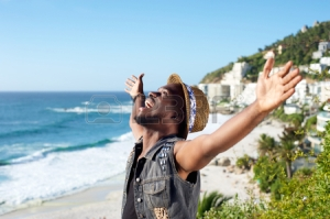37338078-portrait-of-a-happy-african-american-man-with-arms-outstretched-by-the-beach